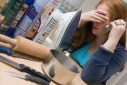 Upset woman on the phone surrounded by a selection of household products used for domestic abuse,