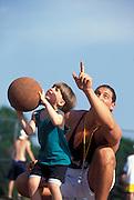 Youth coach teaches basketball to boy.