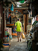 07 APRIL 2016 - BANGKOK, THAILAND: A resident walks through the squatters' community in Mahakan Fort. Mahakan Fort was built in 1783 during the reign of Siamese King Rama I. It was one of 14 fortresses designed to protect Bangkok from foreign invaders, and only of two remaining, the others have been torn down. A community developed in the fort when people started building houses and moving into it during the reign of King Rama V (1868-1910). The land was expropriated by Bangkok city government in 1992, but the people living in the fort refused to move. In 2004 courts ruled against the residents and said the city could take the land. The final eviction notices were posted last week and the residents given until April 30 to move out. After that their homes, some of which are nearly 200 years old, will be destroyed.       PHOTO BY JACK KURTZ