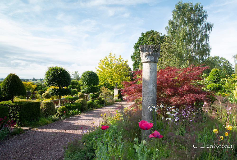 A carved stone column surrounded by papaver and leucanthemum at The Laskett Gardens, Much Birch, Herefordshire, UK
