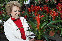 Senior woman looking at flowers in garden center