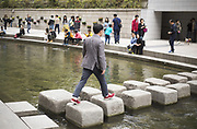Kang (C), who wants to be known only with his family name and came to South Korea in 2003 after he left North Korea, crosses a stream on stepping-stones during an interview in Seoul, South Korea, October 3, 2017. The North Korean defector living in the capital of the South, Kang, did not want his face to be photographed because of security of his family members who live in the North. Photo by Lee Jae-Won (SOUTH KOREA) www.leejaewonpix.com