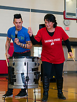 Justin Spencer of Recycled Percussion gives Whitney McCallum a go on the drum during their surprise visit to Laconia Middle School Monday afternoon.  (Karen Bobotas/for the Laconia Daily Sun)
