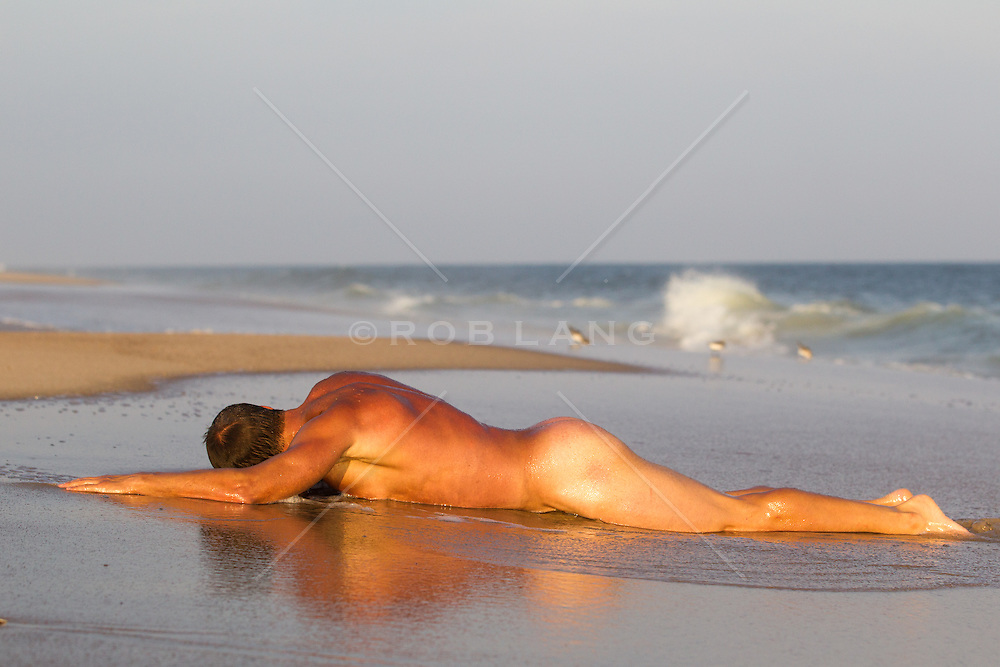 sexy nude man relaxing on the beach by the shore
