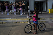 A resident watches as students of the Manguinhos community ballet stretch  prior a  ballet class outside a public library in Manguinhos neighbourhood, Rio de Janeiro, Brazil, Monday, June 11, 2018. The Manguinhos community ballet has been a reprieve from the violence and poverty that afflicts its namesake neighborhood for hundreds of girls who have benefitted from free dance classes since 2012. (Dado Galdieri for The New York Times)