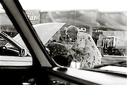 IPLM0135 , South Africa, Ficksburg. March 2003. An elderly lady peers under the hood of her car at a service station in Ficksburg Free State. AFR001; Afrikaner; Aged; Car; Engine; transport; Afrikaans. Leonie Marinovich/South
