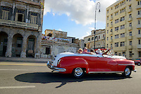 Tourists ride in the back of a red vintage car on the Malecon, the seaside promenade in Havana, Cuba.
