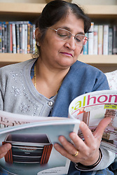 Older woman at home reading a magazine,