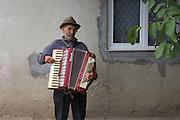 A Roma man plays the accordion outside his home in the all-Roma village of Unguruaia in Cristesti Community, Botosani County, Romania.