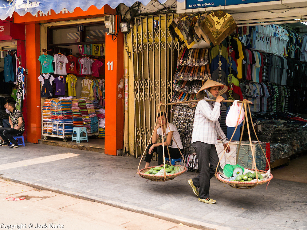 02 APRIL 2012 - HANOI, VIETNAM: A woman selling fruit walks down a sidewalk in Hanoi, the capital of Vietnam.    PHOTO BY JACK KURTZ