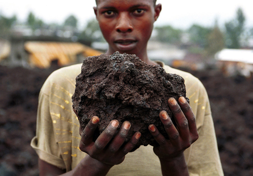 A boy in Goma, Democratic Republic of Congo, holds up a piece of lava deposited following the eruption of the Nyiragongo volcano. Goma, a city of 400,000 people was totally destroyed following the eruption..