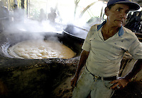 """Alvaro Murillo guards a melting pot where the sugarcane juice boils at the watermill powered-sugarcane process plant """"Los Trapiches"""" on Saturday, January 6th, 2007. in Tacares,  about 25 miles West from San Jose, Costa Rica. Los Trapiches was founded 101 years ago and still produces handcrafted toffee, melaza, and other sugarcane by-products, daily consumed by Costa Ricans. (Photo/Cristobal Herrera)"""