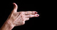 Senior woman's hands making shooting gesture against black background