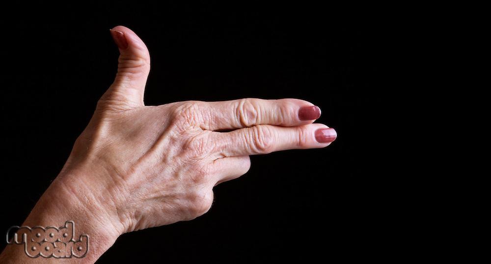 Senior woman's hands making shooting gesture against black background