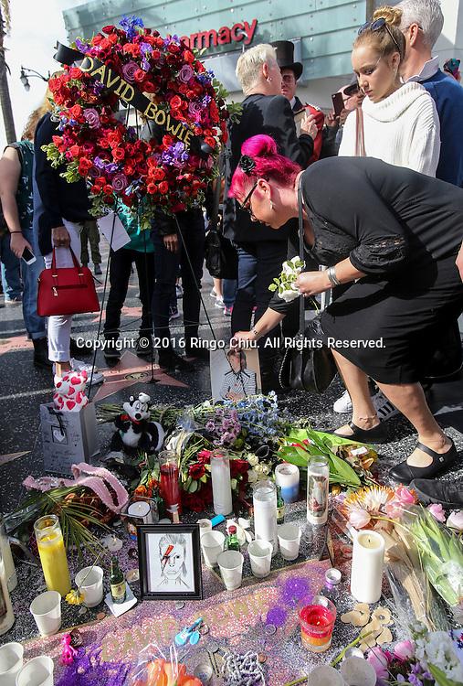 1月11日,在美国洛杉矶,歌迷将鲜花、蜡烛和留有文字的纸条放置在好莱坞星光大道大卫&middot;鲍伊(David Bowie)的星旁。英国传奇歌手大卫鲍伊与病魔抗争18个月后今天病逝,享寿69岁。新华社发 (赵汉荣摄)<br /> People pay their respects with flowers, photographs and message at the Hollywood Walk of Fame star of David Bowie in Los Angeles, Monday, Jan. 11, 2016. Bowie, the other-worldly musician who broke pop and rock boundaries with his creative musicianship, nonconformity, striking visuals and a genre-spanning persona he christened Ziggy Stardust, died of cancer Sunday. He was 69 and had just released a new album. (Xinhua/Zhao Hanrong)(Photo by Ringo Chiu/PHOTOFORMULA.com)<br /> <br /> Usage Notes: This content is intended for editorial use only. For other uses, additional clearances may be required.