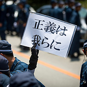 OKINAWA, JAPAN - AUGUST 19 : Anti U.S base protesters is seen with placards guarded by police after staging a sit-in protest against the construction of helipads in front of the gate of U.S. military's Northern Training Area in the village of Higashi, Okinawa Prefecture, on August 19, 2016. Japanese government resume construction of total six helipads in a fragile ten million year old Yanbaru forest that is home to endemic endangered species such as the Okinawan rail and Okinawan wood pecker. (Photo by Richard Atrero de Guzman/NURPhoto)