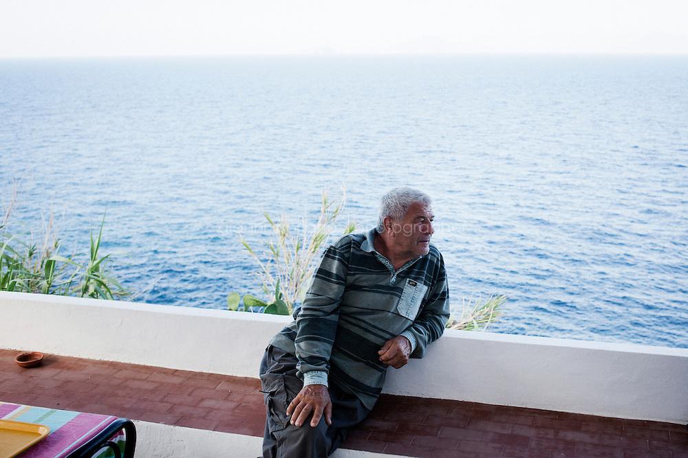 GINOSTRA (ME), ITALIA - 14 GIUGNO 2013: Salvatore, 67 anni, proprietario del Bar Ristorante &quot;L'incontro&quot;, &egrave; qui seduto nella terrazza del locale, a Ginostra il 14 giugno 2013.<br /> <br /> Karol Hoffman, che vive da 30 anni insieme ad altri connazionali a Ginostra, considerato che il governo nazionale non ha mai provveduto a risolvere il problema di una centrale fotovoltaica malfunzionante, ha lanciato un appello alla Cancelliera Angela Merkel.