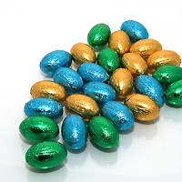 Foil wrapped mini chocolate Easter eggs  against a shiny white background.<br />
