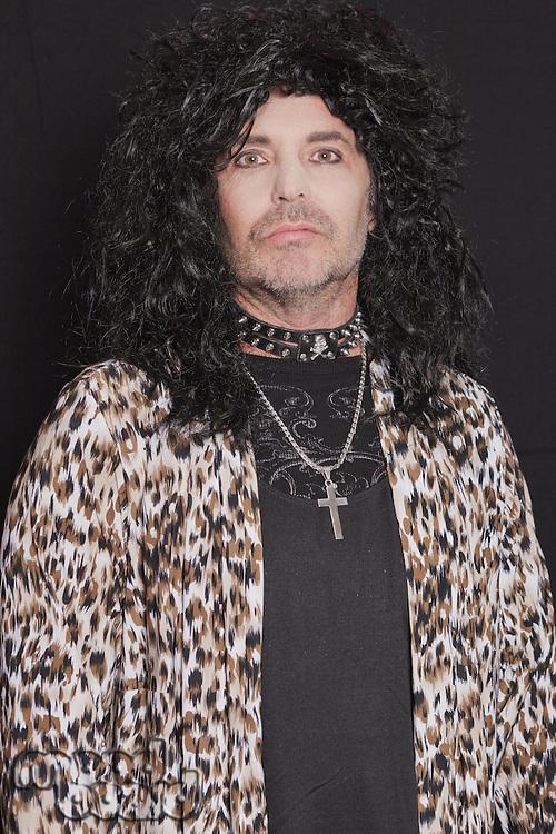 Portrait of middle-aged man wearing leopard skin pattern over black background