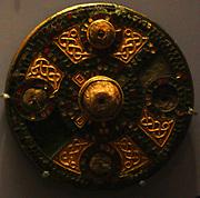 Escutcheons, gilt copper alloy.  600 Spelsbury and Standlake, Oxfordshire.  Jewelled disc brooch, silver, gold, glass gardet. 550-650, Faversham, Kent