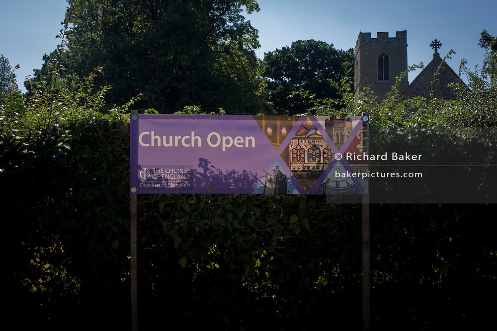 Church Open banner on display outside the flint wall architecture of St Michael's Anglican church at Irstead, on the Norfolk Broads.