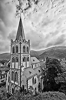 Black and White view of St Peter Church, and includes birds, mountains and cloudy skies in the background, Bacharach, Germany.