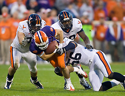 November 21, 2009; Clemson, SC, USA;  Clemson Tigers quarterback Kyle Parker (11) is tackled by Virginia Cavaliers linebacker Cam Johnson (56) and nose tackle Nate Collins (98) and defensive end Matt Conrath (94) during the third quarter at Memorial Stadium. Clemson defeated Virginia 34-21.