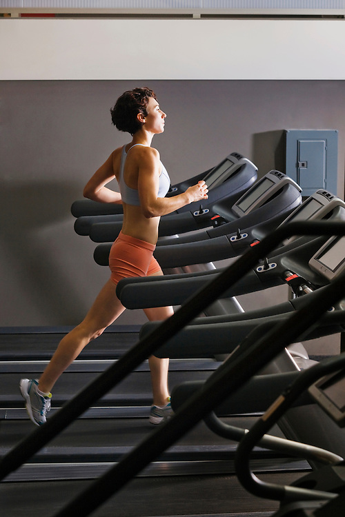 Late 20's woman running in a healthclub on a treadmill.