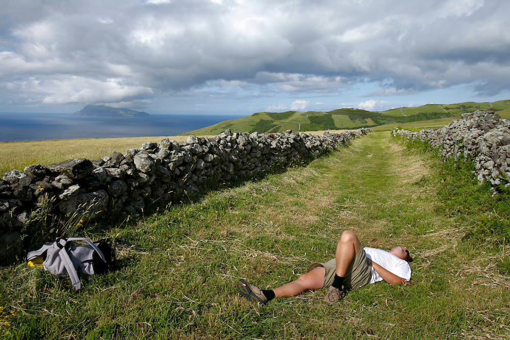 A tourist rests in a footway in Flores island. Corvo island can be seen in the distance.