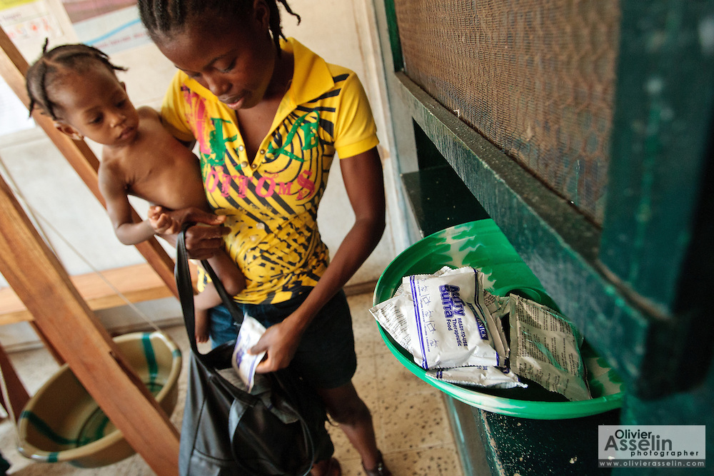 Theresa Kollie, 24, holds her daughter Musu Kollor, 11 months old, who suffers from malnutrition, as she receives a weekly supply of ready-to-eat therapeutic food at the Slipway clinic in Monrovia, Montserrado county, Liberia on Monday April 2, 2012.