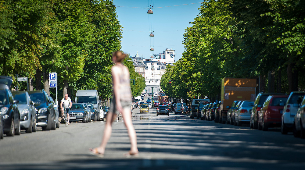 A young woman crosses the road on Frederiksberg Allé. The tree-lined boulevard runs from Frederiksberg Have down towards Føtex on Vesterbrogade