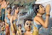 A colorful painted wall with detailed female releif sculptures is on display at a Buddhist temple in Luang Prabang, Laos. Luang Prabang is a UNESCO World Heritage City.