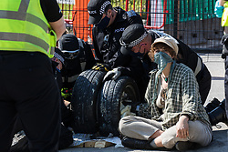 West Hyde, UK. 14th September, 2020. Officers from Hertfordshire Police's cutting team work to remove environmental activists from HS2 Rebellion using a lock-on arm tube to block a gate to the South Portal site for the HS2 high-speed rail link. Anti-HS2 activists blocked two gates to the site for the controversial £106bn rail link, one remaining closed for over six hours and another for over twelve hours.