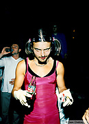 Man wearing a pink dress holding a bottle of Coca Cola and Marlboro cigarettes Ibiza 1999