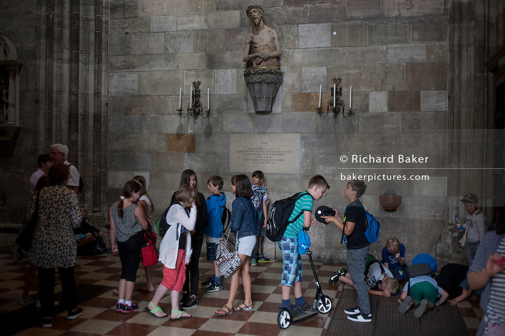 An accompanied group of Austrian schoolchildren mess about below an effigy of Christ in St. Stephen's Church on 28th June 2016, in Vienna, Austria. While some chat among themselves, others are on their knees to inspect below the floor through the gaps of a grating. St. Stephen's Cathedral is the mother church of the Roman Catholic Archdiocese of Vienna and stands on the ruins of two earlier churches, the first a parish church consecrated in 1147. The most important religious building in Vienna, St. Stephen's Cathedral has borne witness to many important events in Habsburg and Austrian history. (Photo by Richard Baker / In Pictures via Getty Images)