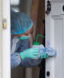 © Licensed to London News Pictures. 24/03/2016. Croydon, UK. A forensics officer inspects the front door to a house where a woman, believed to be in her 20s was found with multiple stab wounds. A man in his 30's has been arrested on suspicion of murder. Photo credit: Peter Macdiarmid/LNP