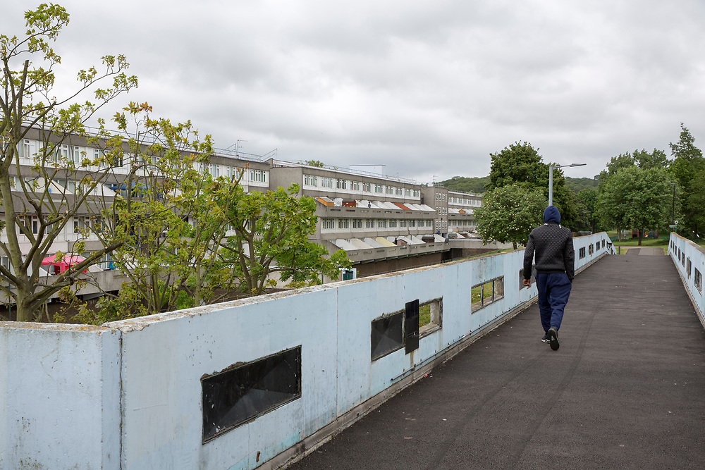 A man walks across a pedestrian walkway connecting tower blocks on Thamesmead Estate, social housing run by the Peabody Trust, Greenwich & Bexley borough, London, UK. (photo by Andrew Aitchison / In pictures via Getty Images)