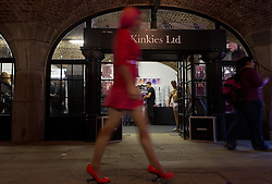 © London News Pictures. 26/10/2013 . London, UK. A woman in pink walks past the Kinkies Ltd shop at the Erotica show at Tobacco Dock in East London on 25 October 2013. The three day event runs from 25 October until 27 October and features stalls selling sex toys and clothes and stage shows of exotic dancing. Photo credit : Vickie Flores/LNP