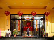 """13 FEBRUARY 2019 - SIHANOUKVILLE, CAMBODIA: A cleaning worker at the BWin Casino, a newly opened casino in downtown Sihanoukville, goes into the casino after cleaning the front entry. There are about 80 Chinese casinos and resort hotels open in Sihanoukville and dozens more under construction. The casinos are changing the city, once a sleepy port on Southeast Asia's """"backpacker trail"""" into a booming city. The change is coming with a cost though. Many Cambodian residents of Sihanoukville  have lost their homes to make way for the casinos and the jobs are going to Chinese workers, brought in to build casinos and work in the casinos.      PHOTO BY JACK KURTZ"""