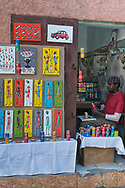 Artist from Senegal in his shop that displays his art with recycled soda cans.