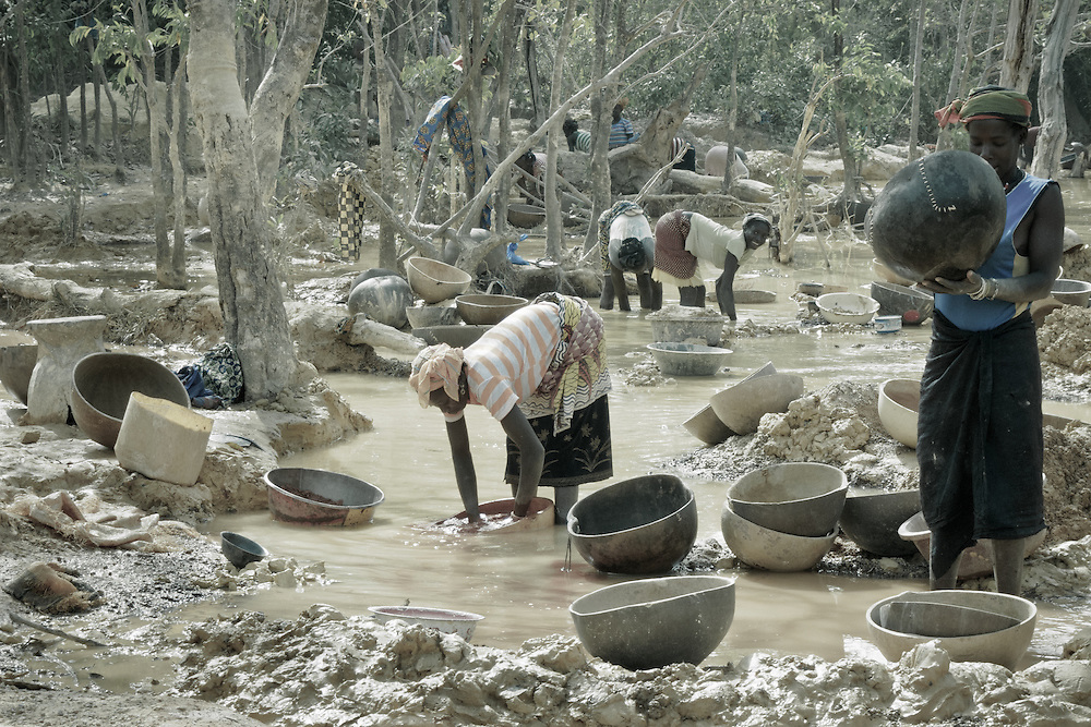 Stock photograph of women in Guinea panning gold from crushed ore using calabashes in a local river.