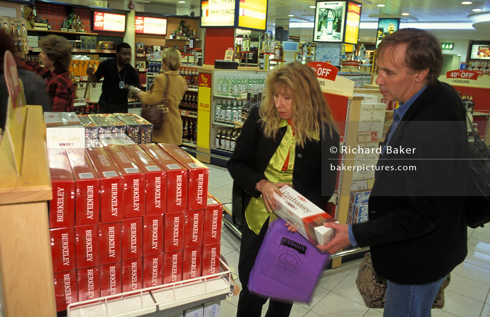 A couple compare prices of cigarette carton brands while shopping before flying from Heathrow Airport, on 8th February 1999, at London, England.