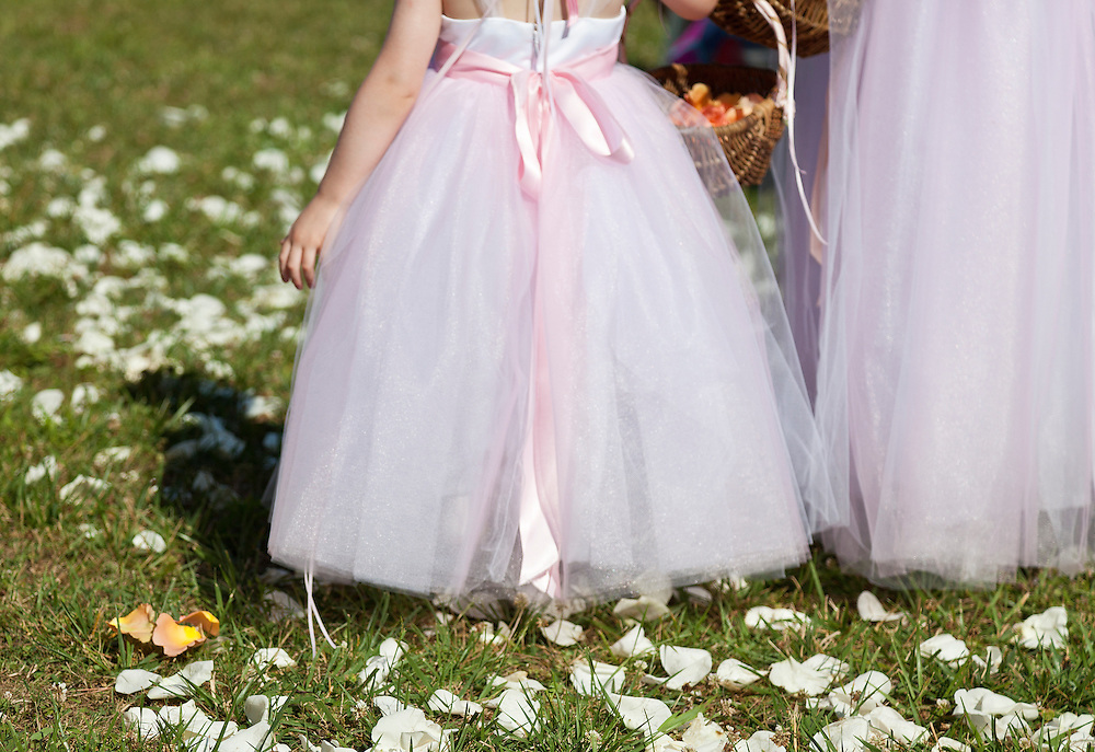 Young girl in pink chiffon bride's maid gown carrying flower basket stands on lawn covered with rose pedals