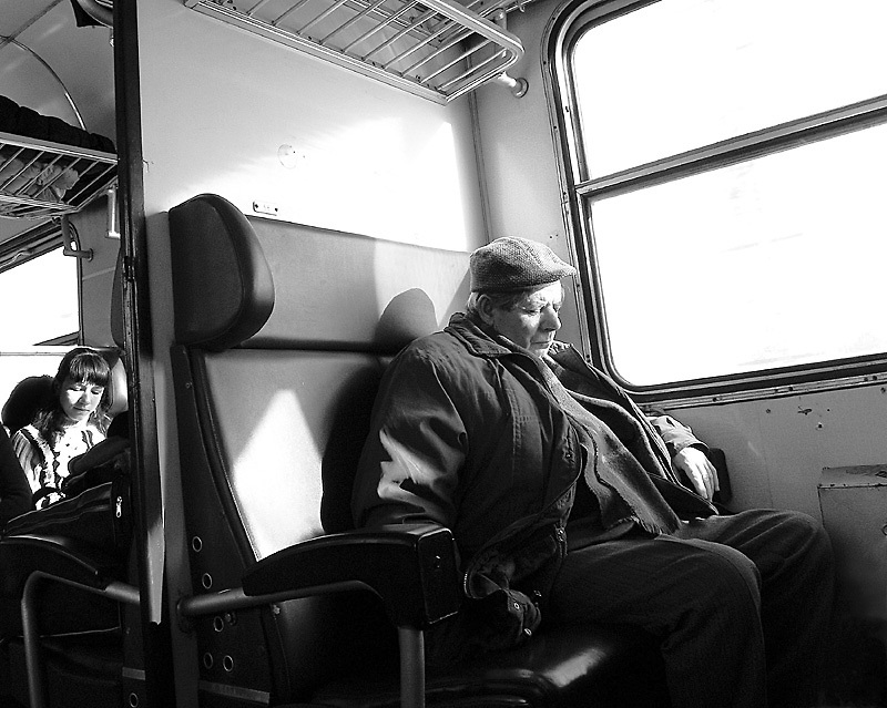 An old man sleeps and a little girl reads on a train coming back to the city from a harvest festival celebration from Neighborhoods series