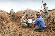 Soldiers help Richard Osgood, MOD Archaeologist to map overgrown trench system in a practice battlefield, where thousands of troops trained before embarking for the battlefields of Europe during World War One. The trench system was been discovered by chance on the Browndown Ministry of Defence site in Gosport, Hampshire, England. March 6, 2014. AFP PHOTO / CHRIS ISON.