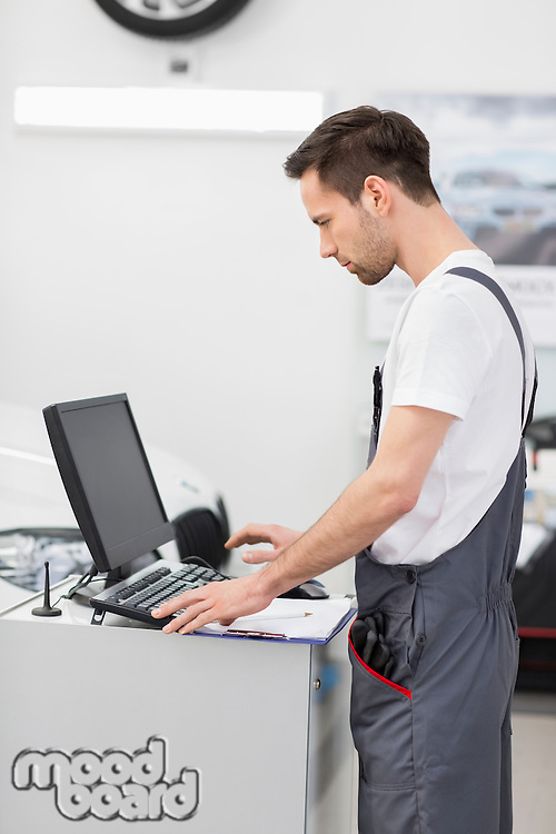 Side view of automobile mechanic using computer in workshop