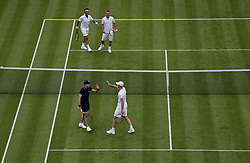 Jamie Murray plays with a ball boy as Goran Ivanisevic takes over his duty against Lleyton Hewitt and Pat Cash on No.1 court at The All England Lawn Tennis Club, London.