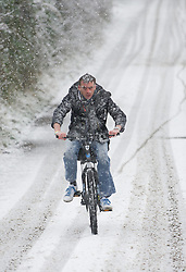 © Licensed to London News Pictures. 14/01/2013..Saltburn, Cleveland, England..A man rides his bicycle through the start of heavy snow in Saltburn, Cleveland today.  ..Photo credit : Ian Forsyth/LNP