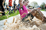 Barbara Siders slides to the finish line on a slip and slide after finishing the Race for a Reason Mud Run. Photo by: Ross Brinkerhoff. Race for a Reason, Race 4 A Reason, Annual Events, Events, Students, Faculty & Staff
