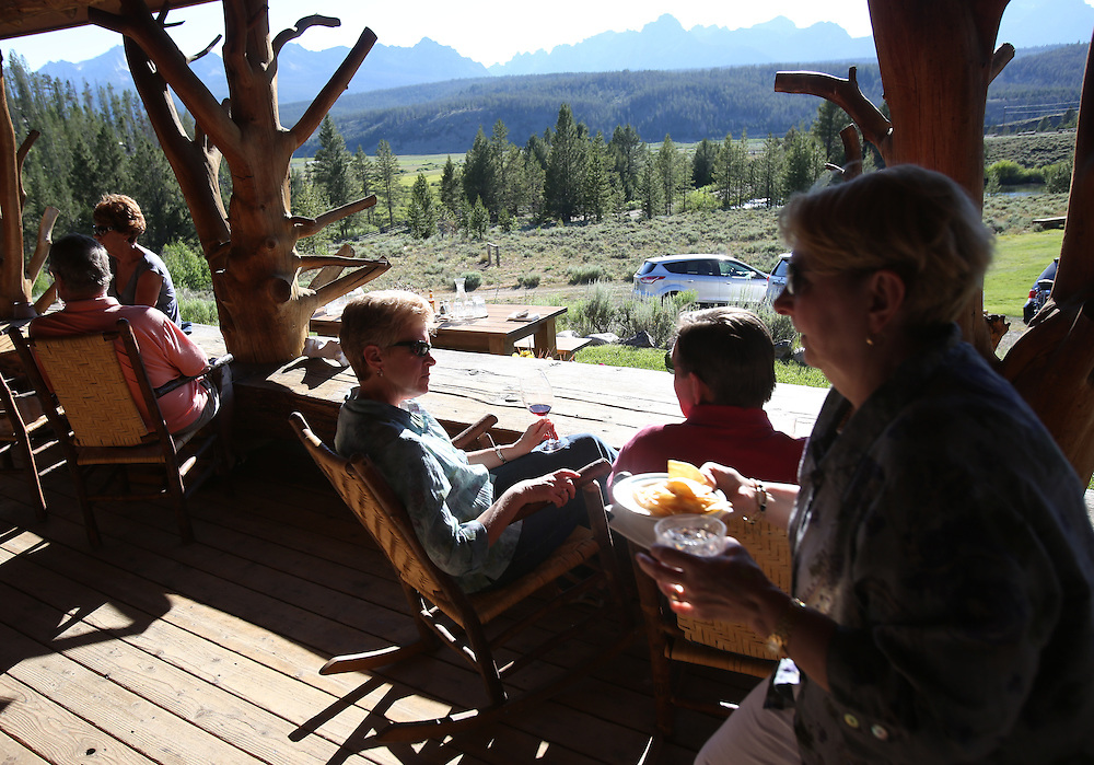 Guests at the Idaho Rocky Mountain Lodge enjoy drinks and hors d' oeuvres on the deck on Saturday July 13, 2013, in the Sawtooth Mountains in central Idaho south of the town of Stanley.